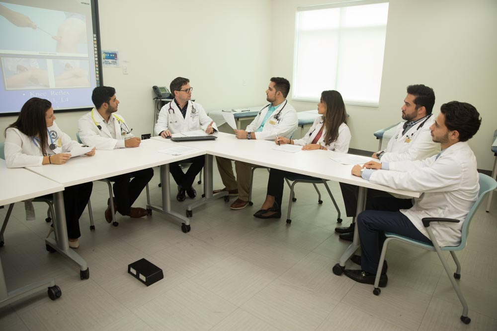 Students sitting around a table during Intro to Clinical Medicine