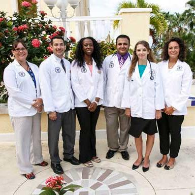 Group of doctors standing in front of flowers and palm trees
