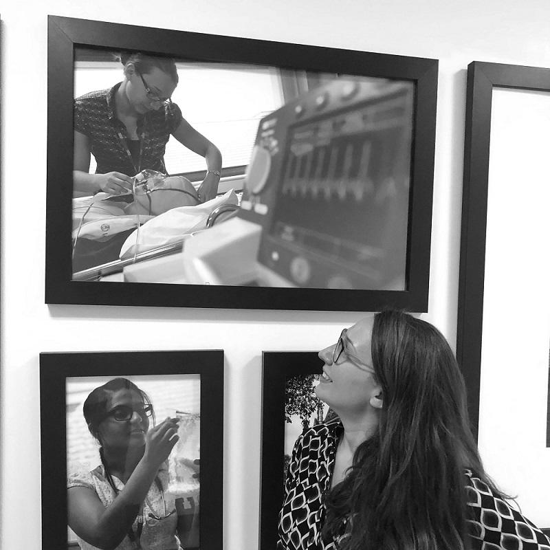 A doctor looks at a photo of herself on the wall